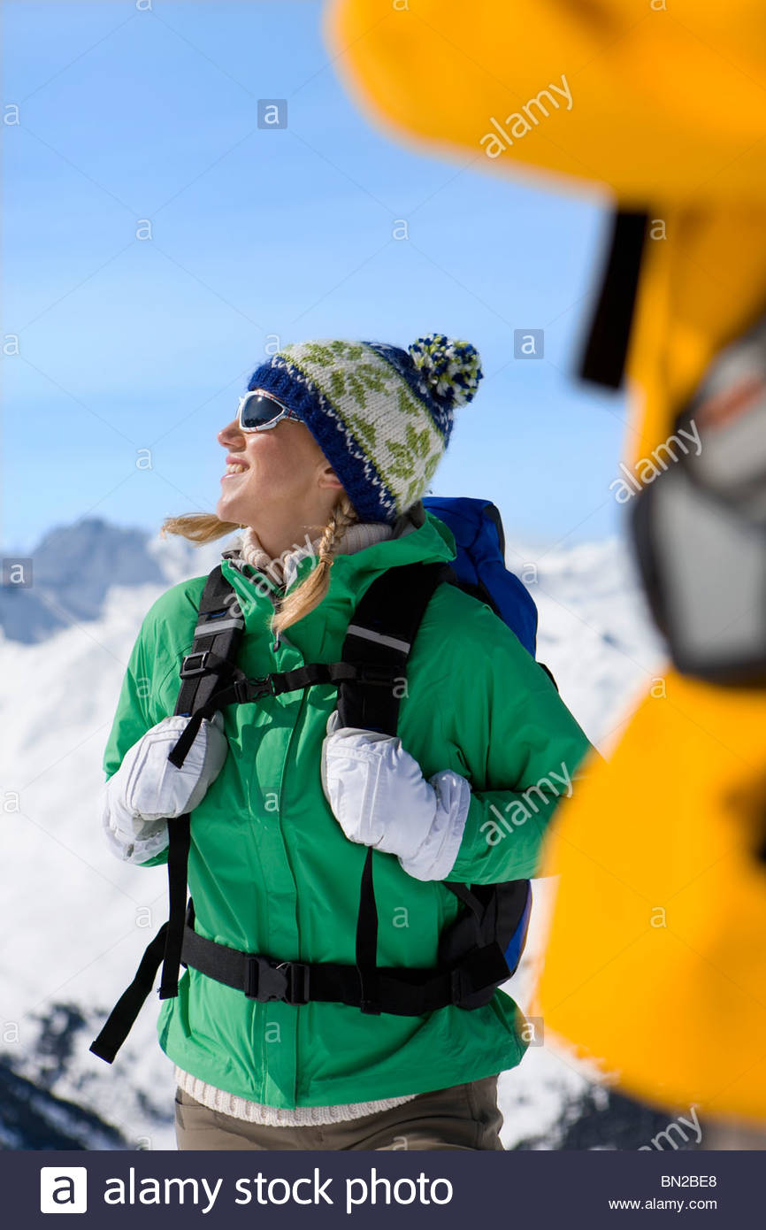 Happy woman with backpack on snowy mountain - Stock Image