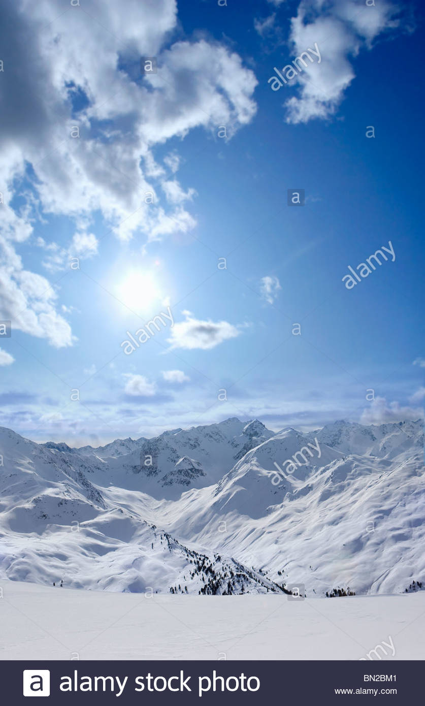 View of snowy mountain range and sun in blue sky - Stock Image