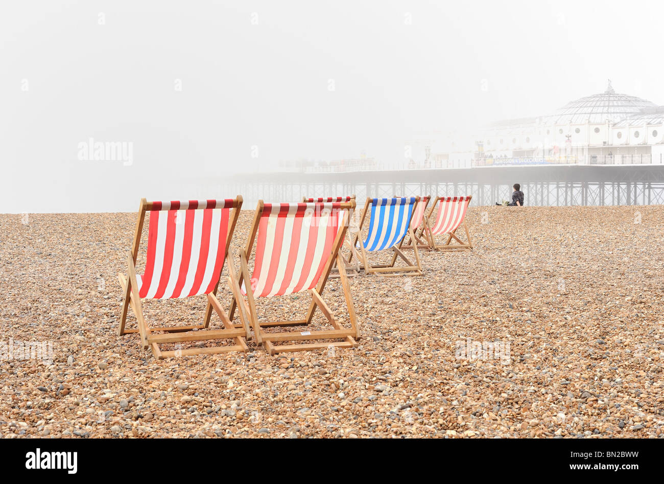 Blue and red deckchairs on a foggy pebble beach with Brighton pier in the background - Stock Image