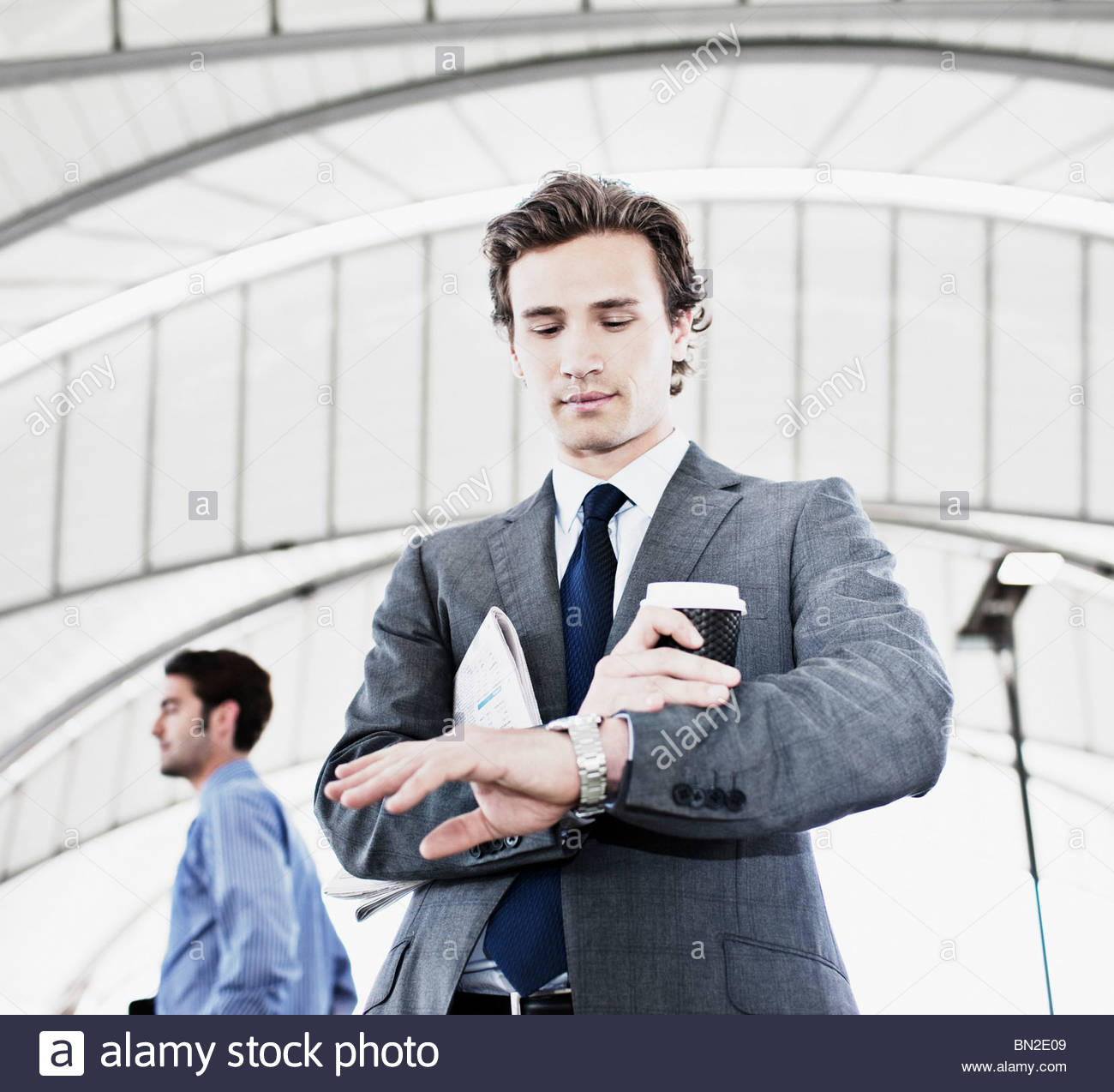 Businessman with coffee checking the time - Stock Image