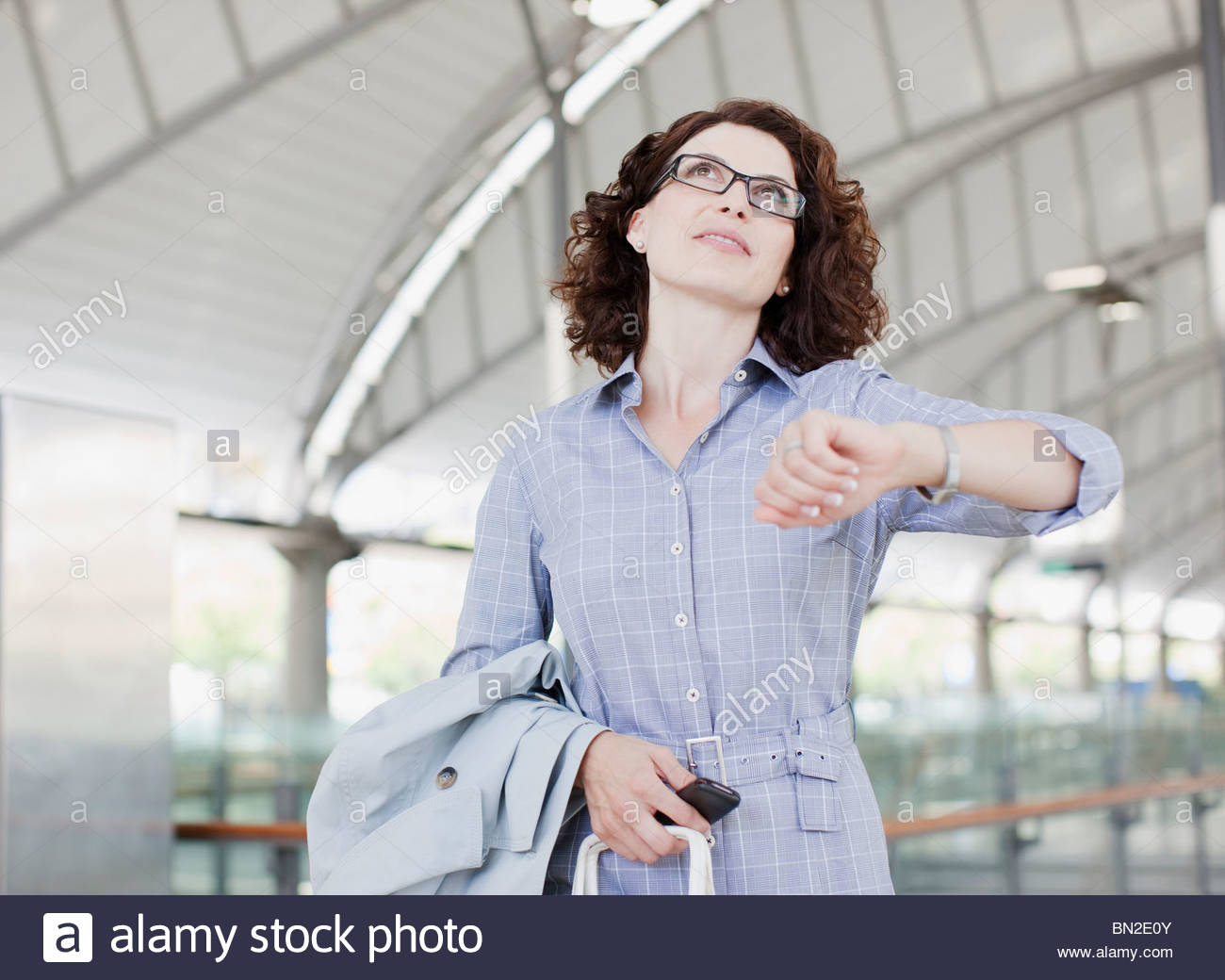 Businesswoman checking the time - Stock Image
