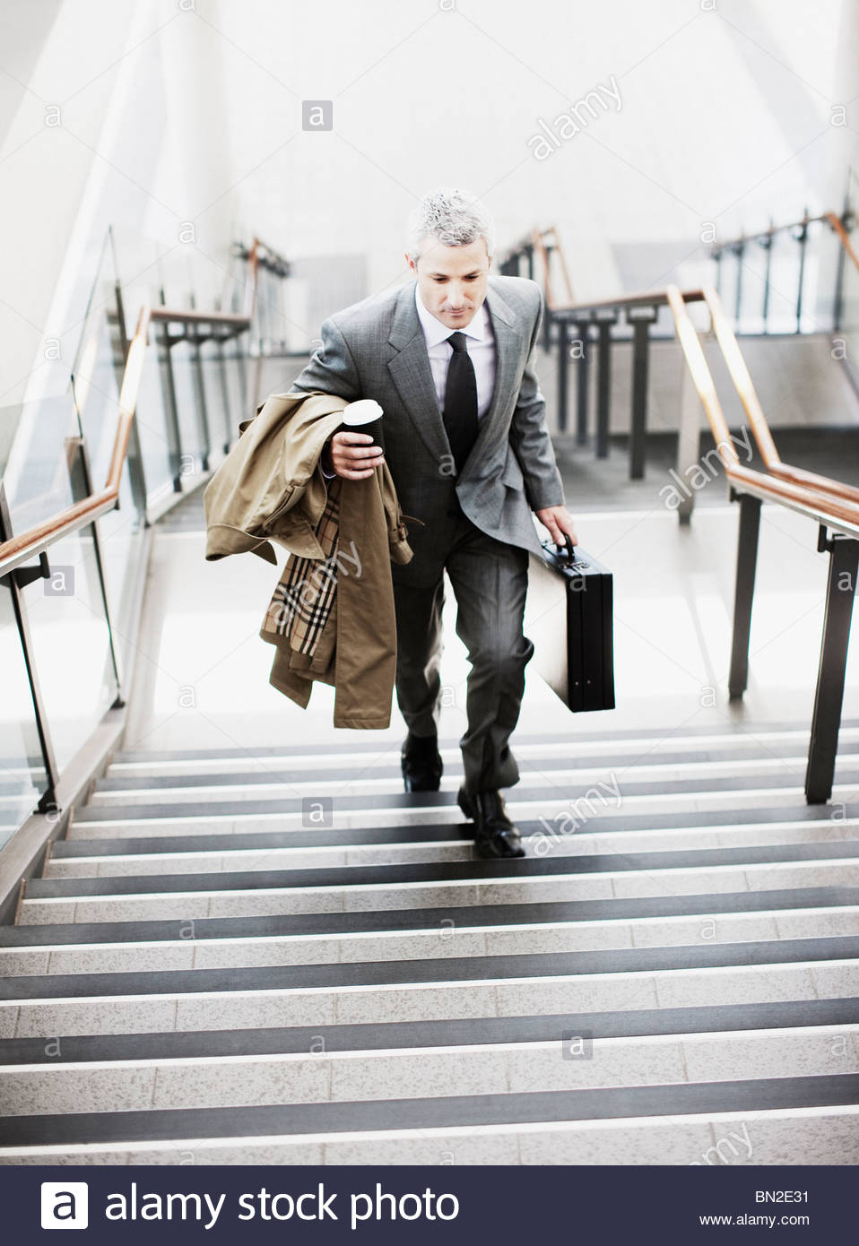 Businessman walking up stairs in train station - Stock Image