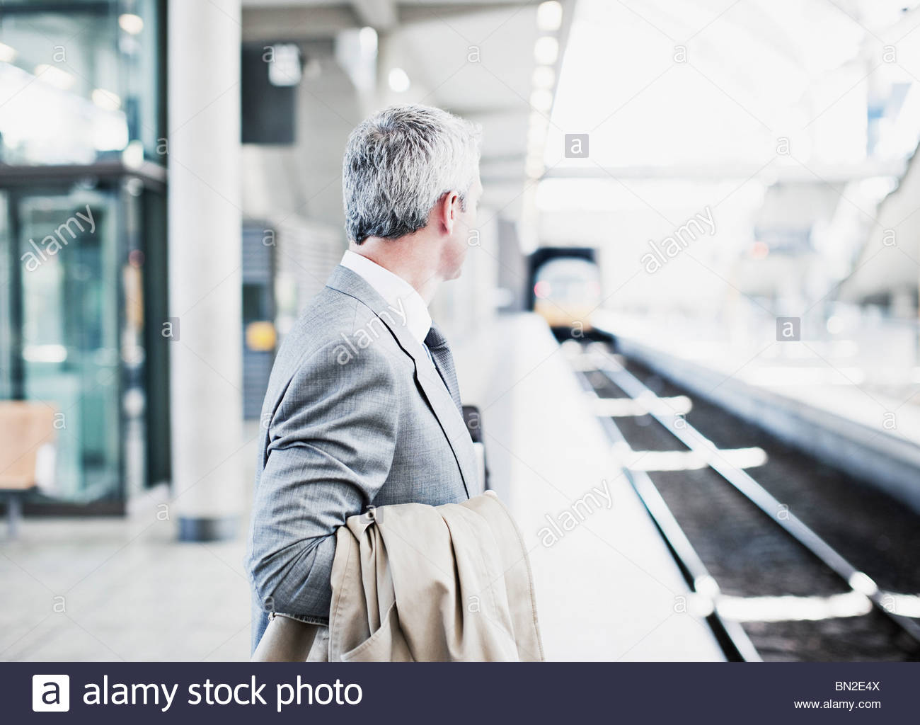 Businessman waiting for train on platform - Stock Image