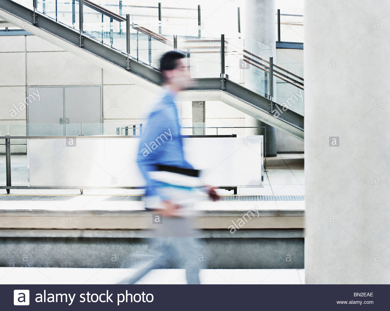 Businessman rushing on train platform - Stock Image