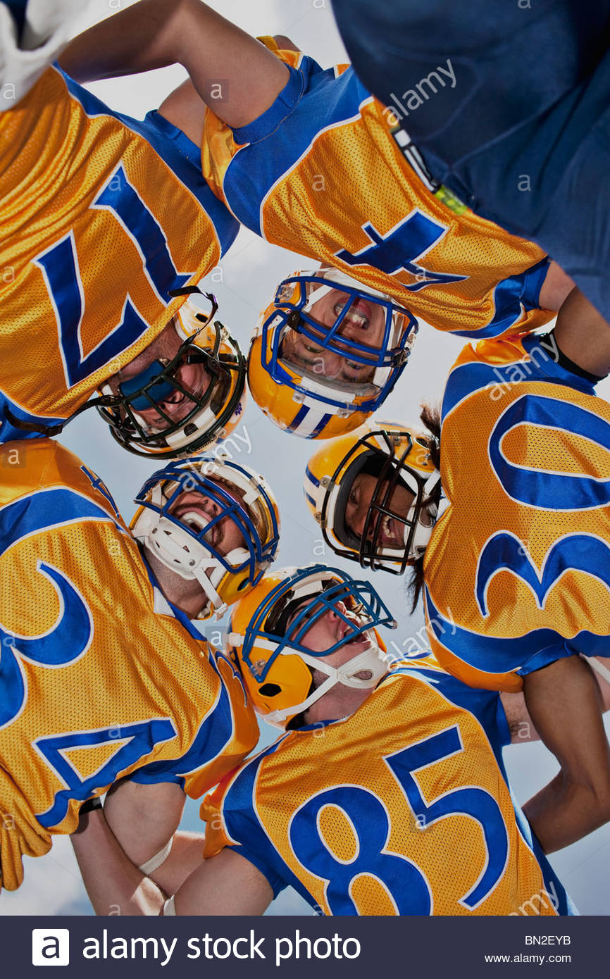 Football players in huddle - Stock Image