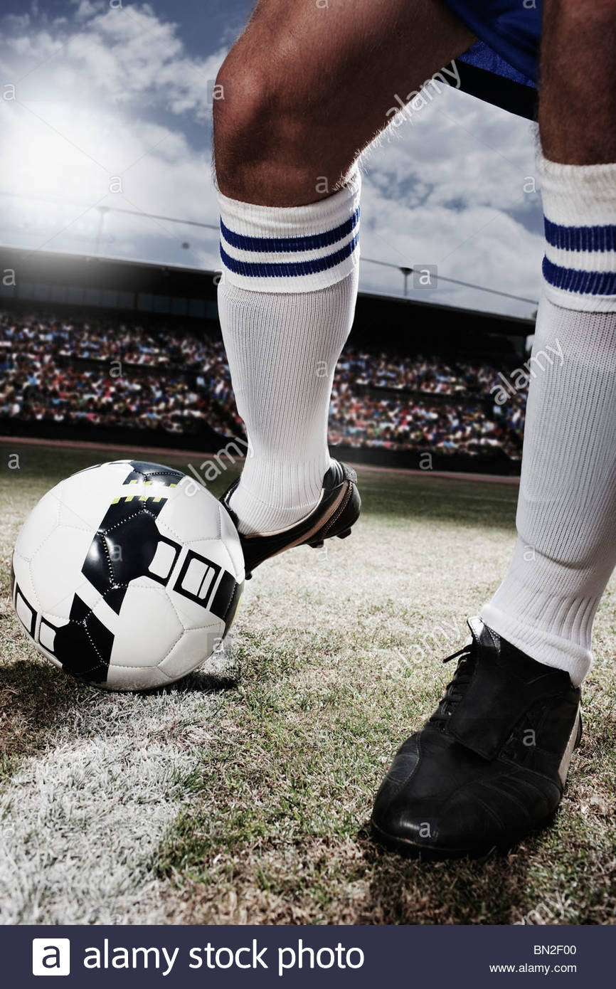 Soccer player kicking soccer ball - Stock Image