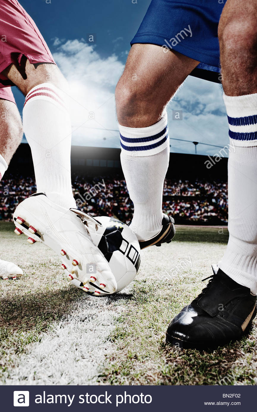 Soccer players competing for soccer ball - Stock Image