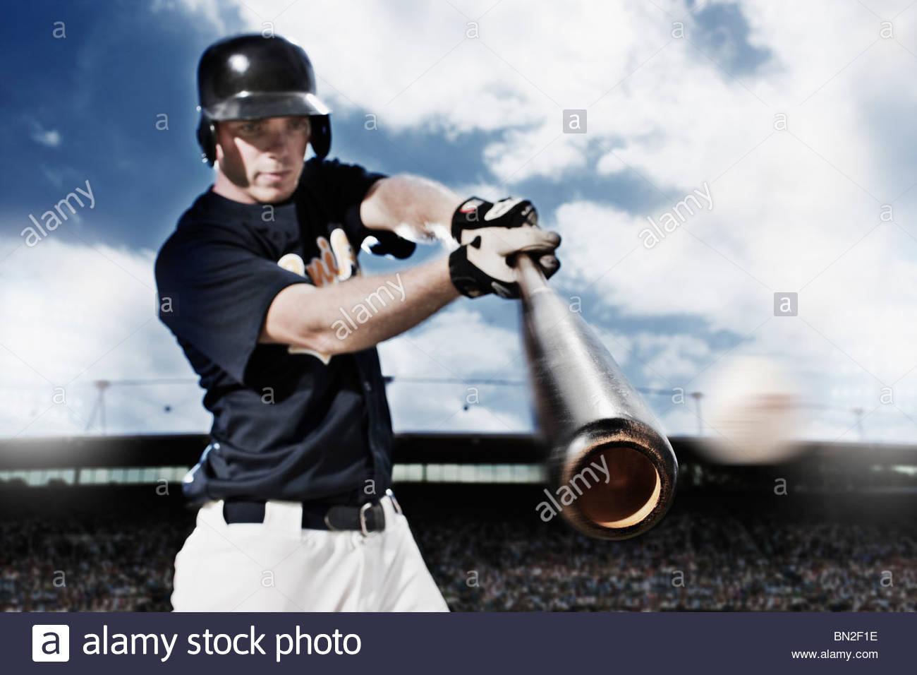 Baseball player swinging baseball bat - Stock Image