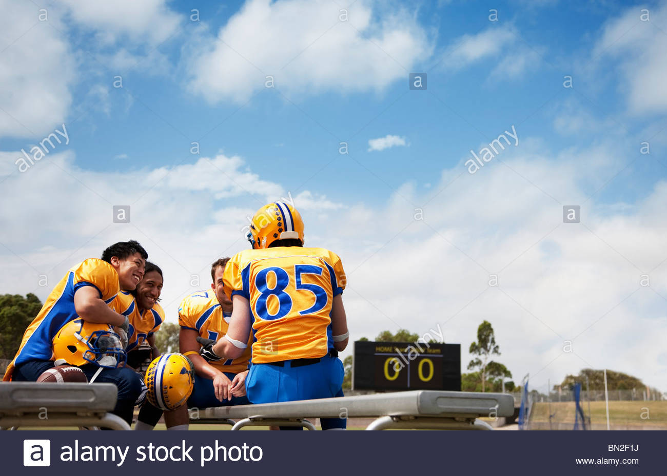 Football players resting on bench - Stock Image