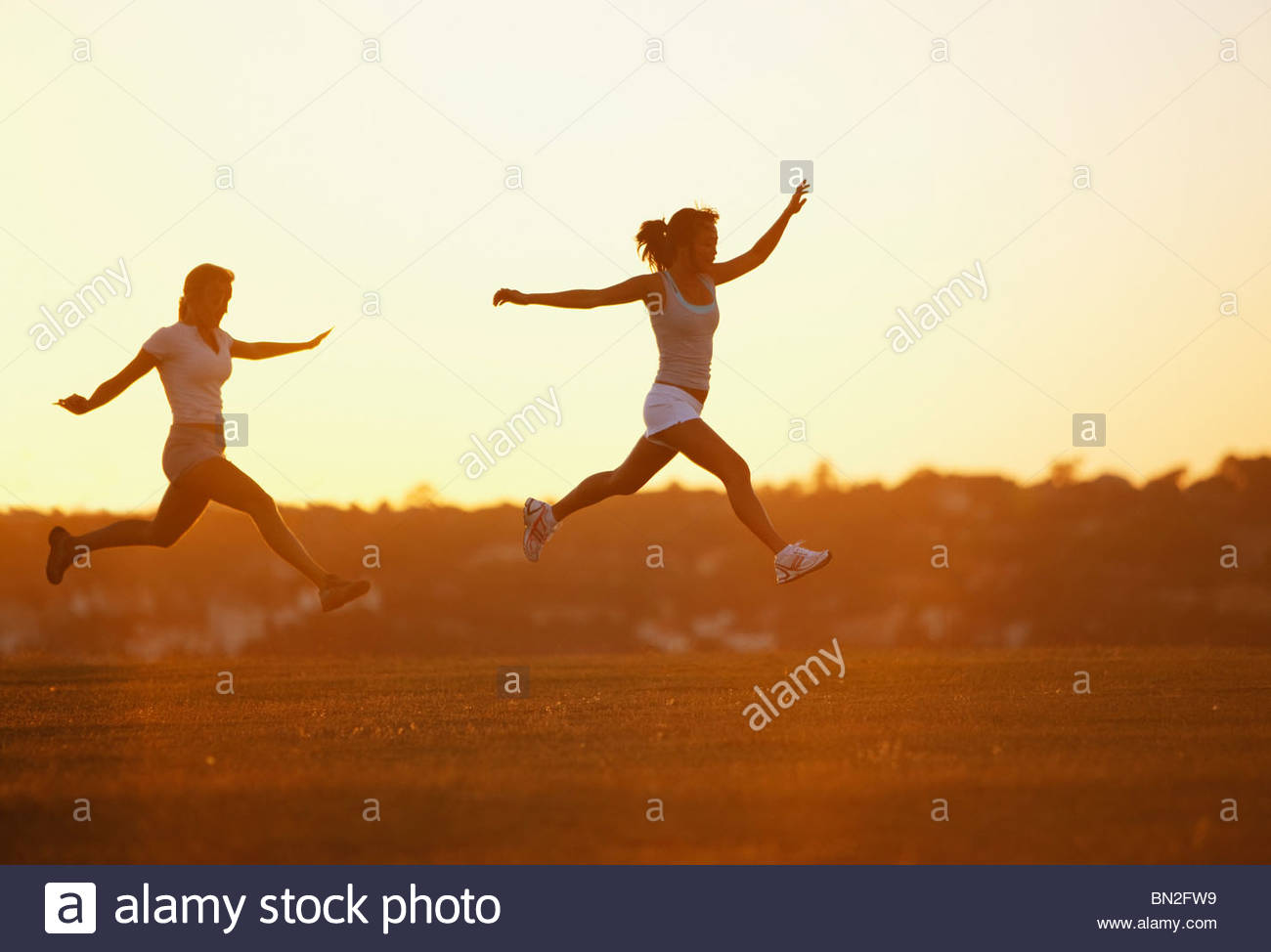 Friends running through park Stock Photo