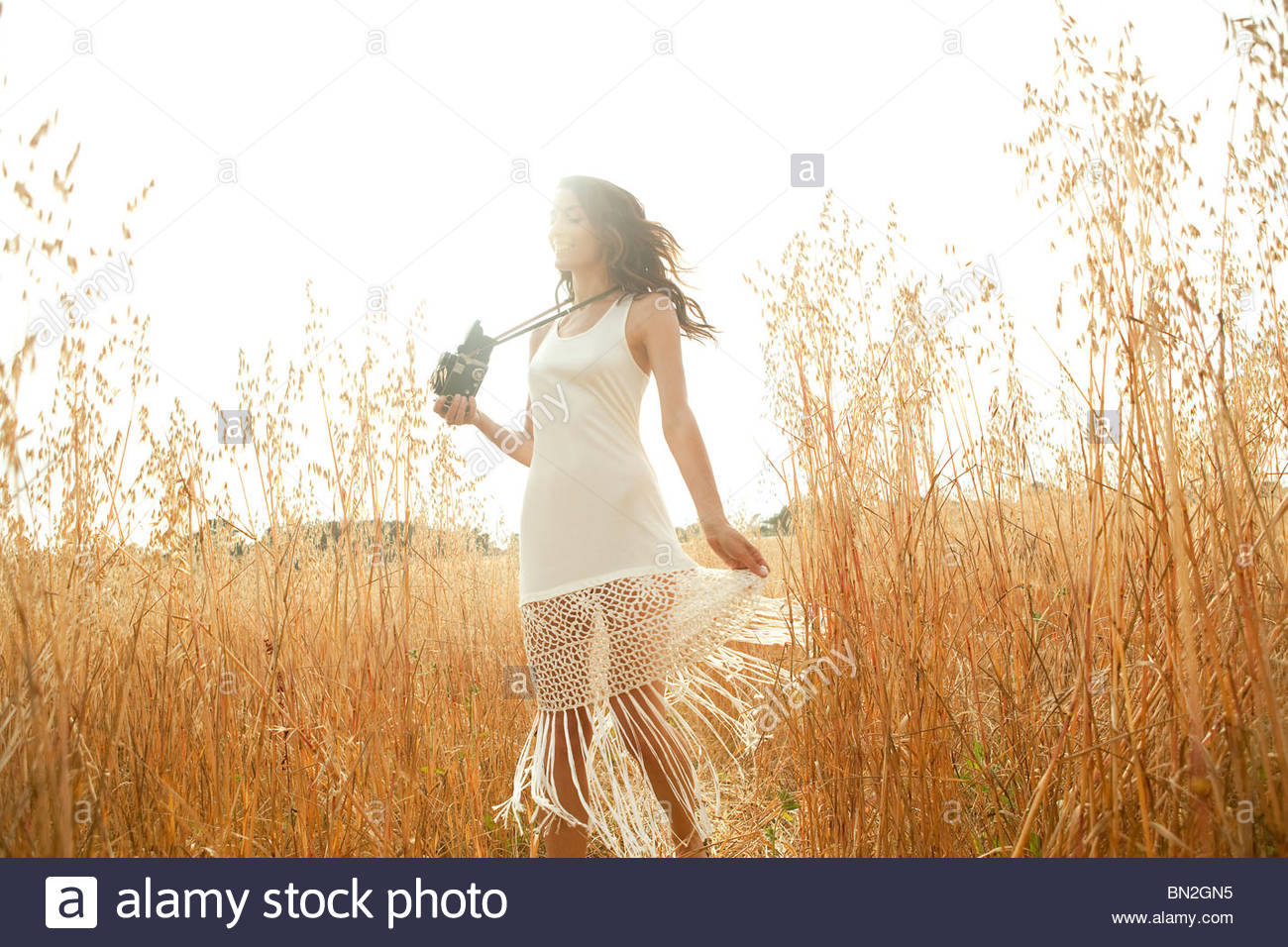 Woman standing in grass with camera Stock Photo
