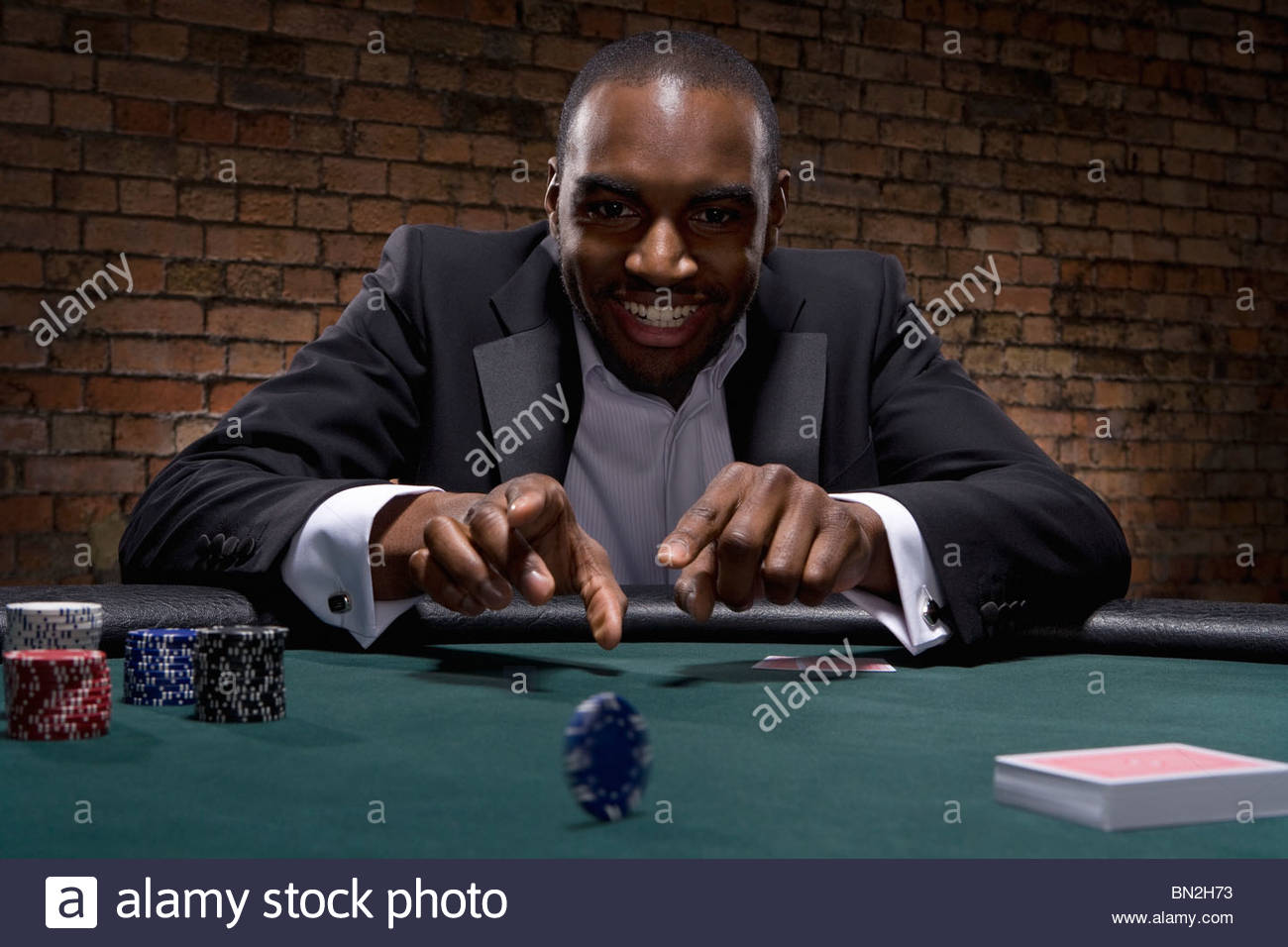 Man rolling poker chip in casino - Stock Image