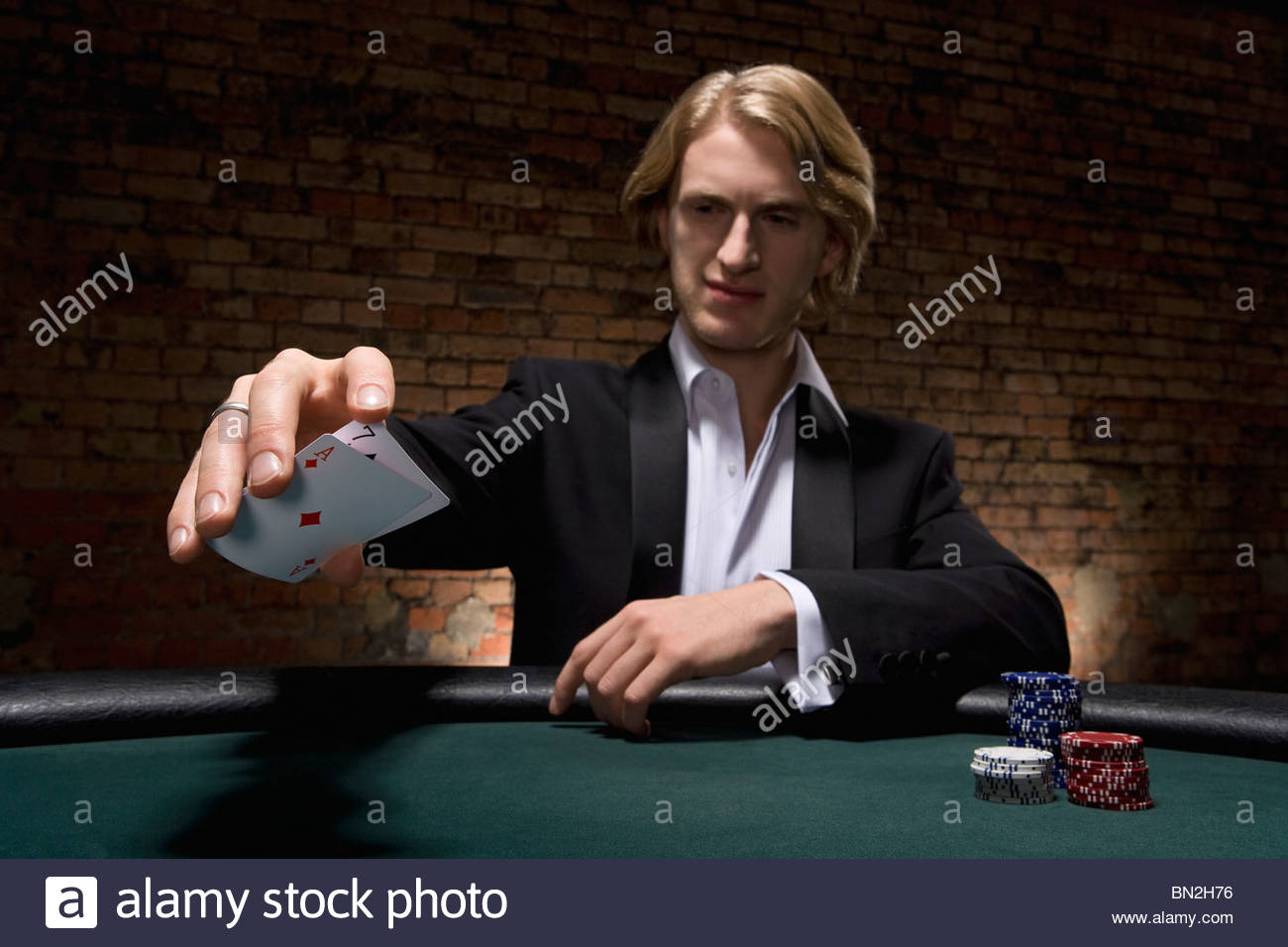 Man dropping cards on table in casino - Stock Image