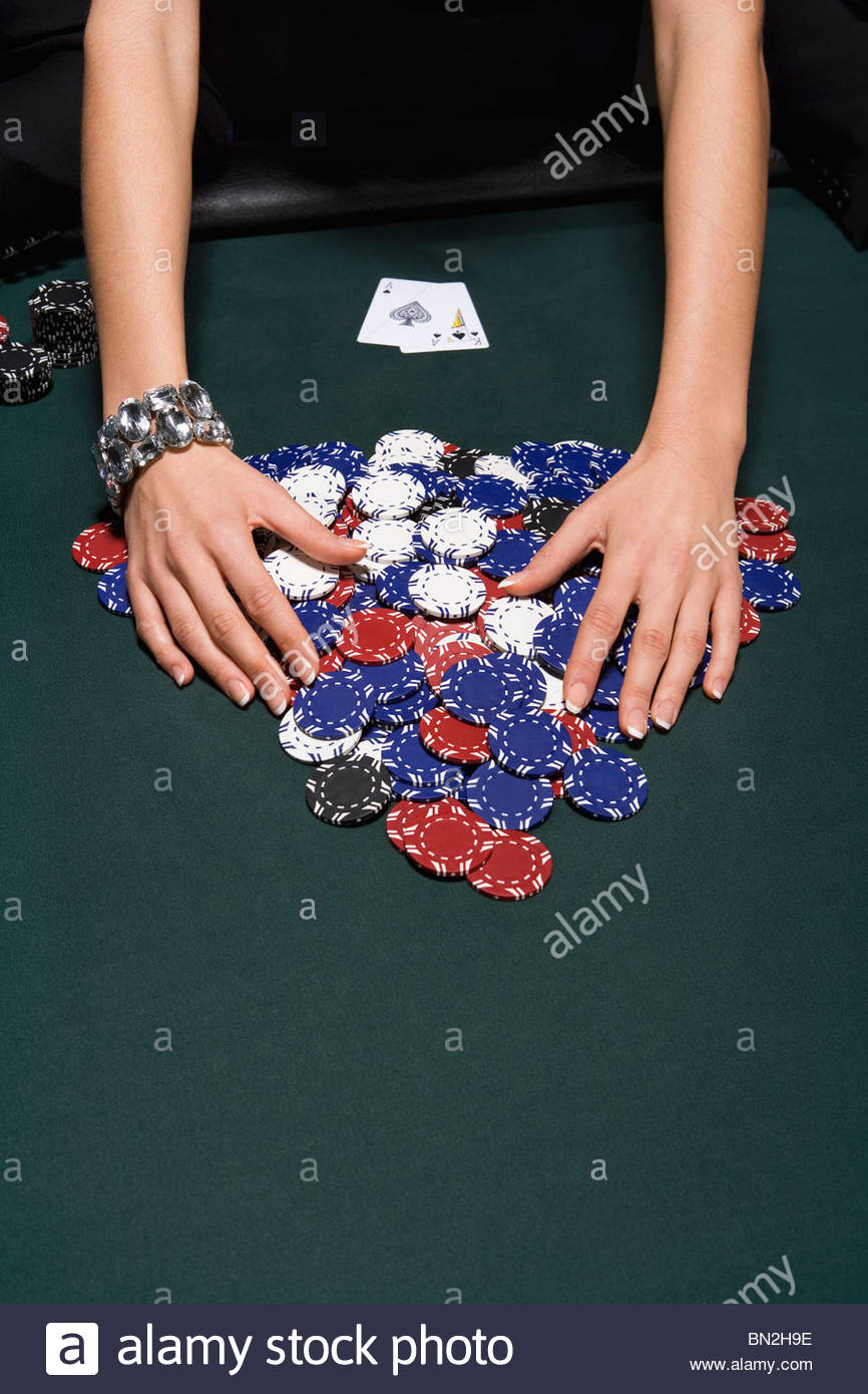 Woman gathering poker chips in casino - Stock Image