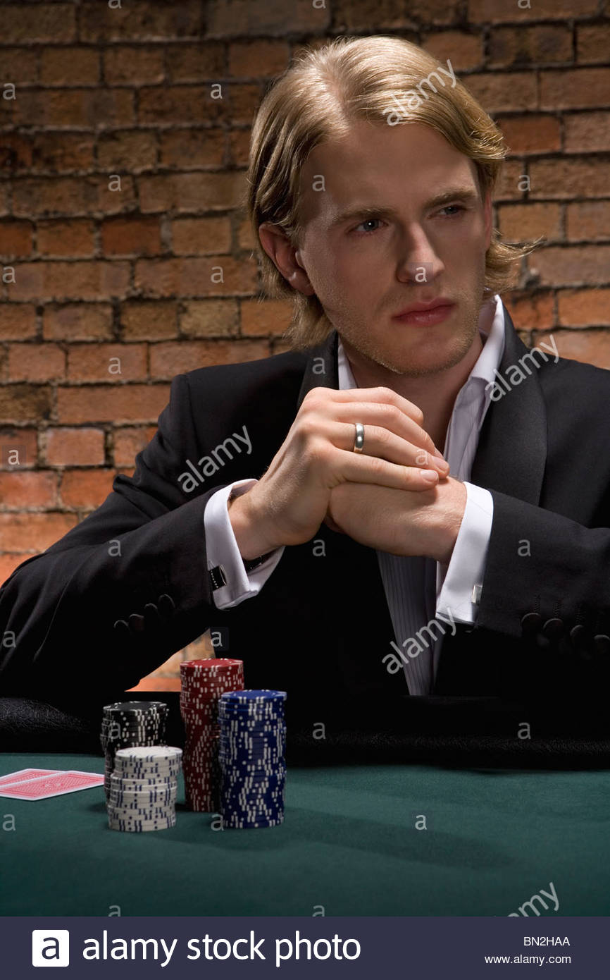 Man playing cards in casino - Stock Image