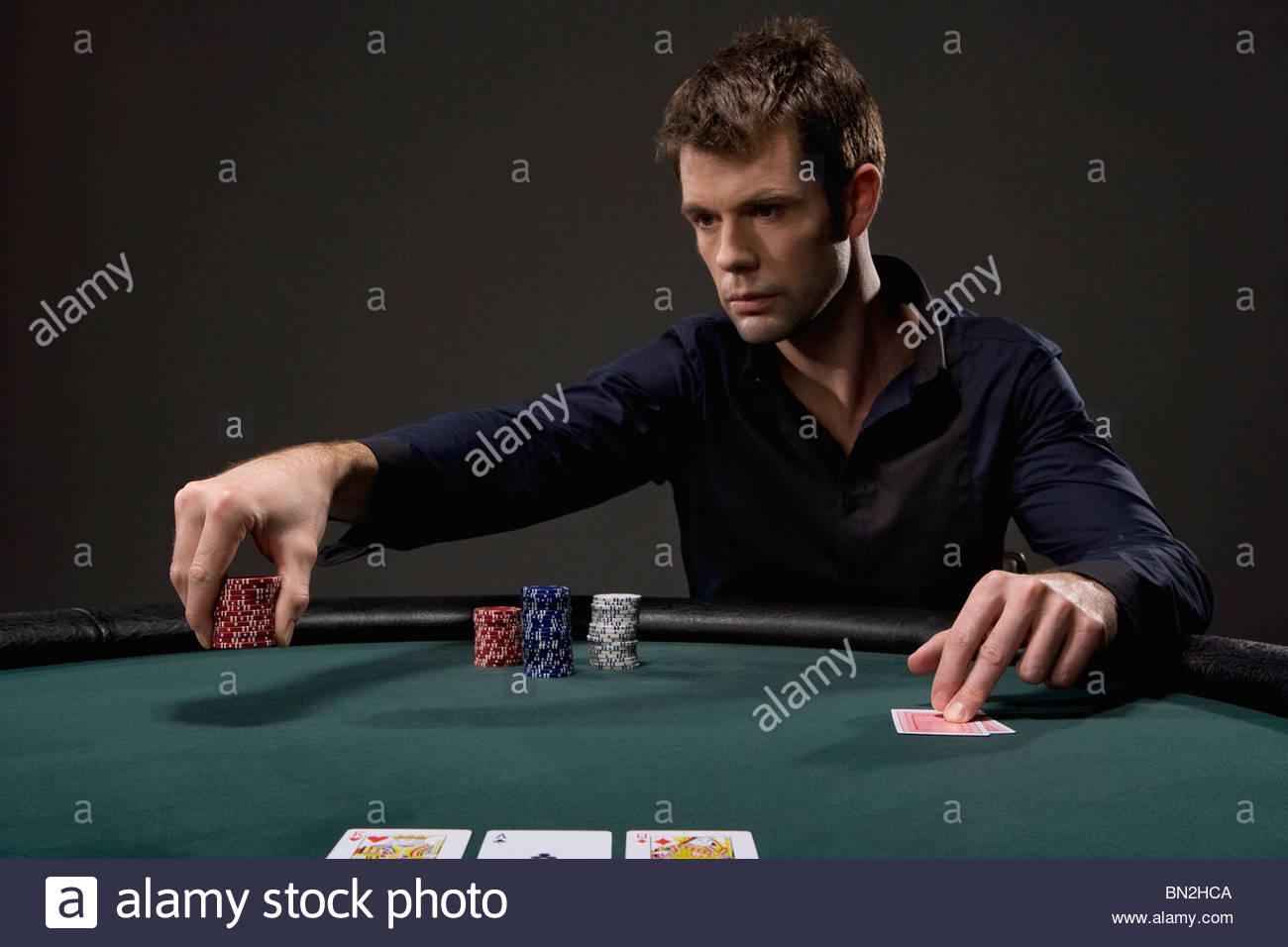 Man playing poker in casino - Stock Image