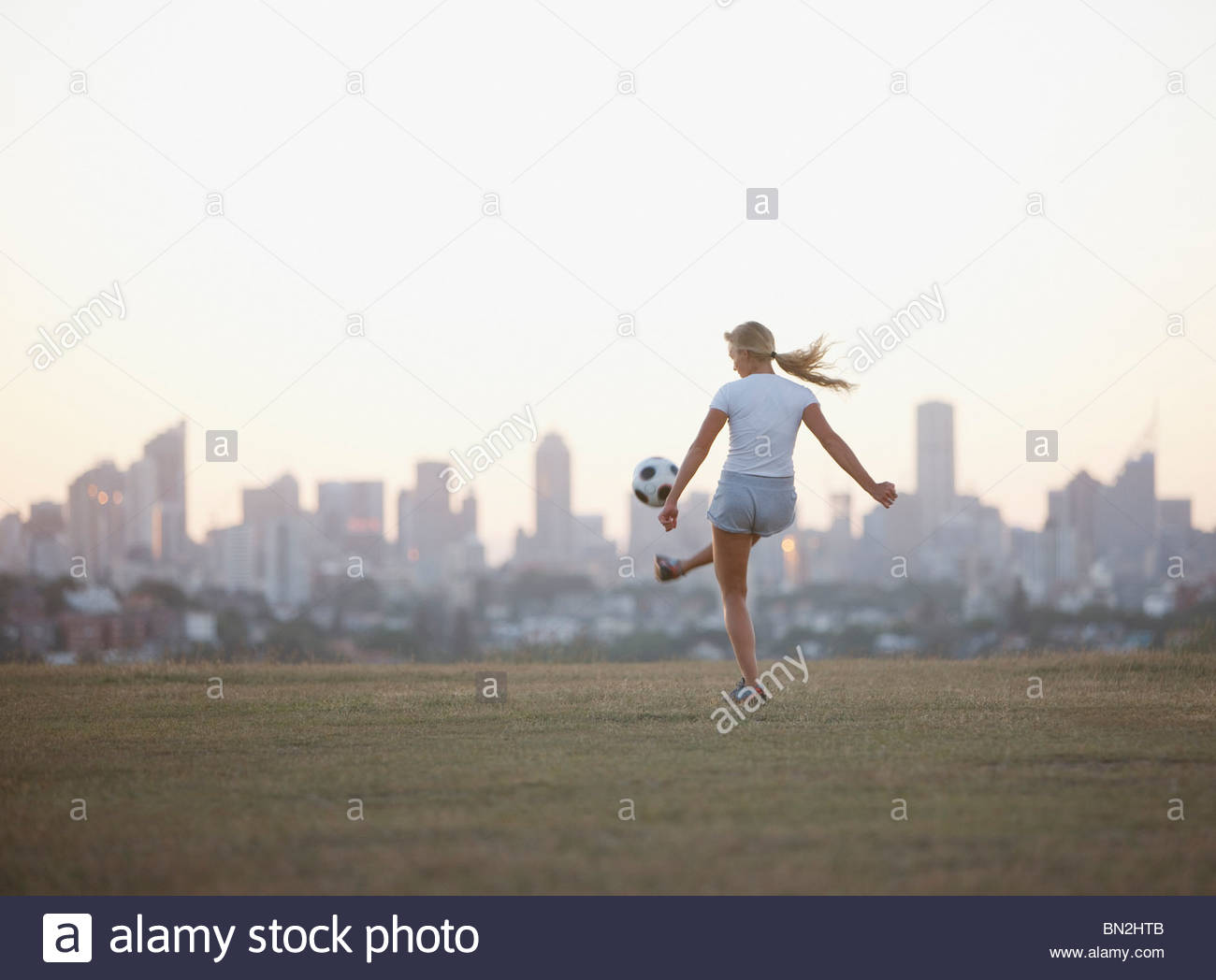 Woman kicking soccer ball in urban park - Stock Image