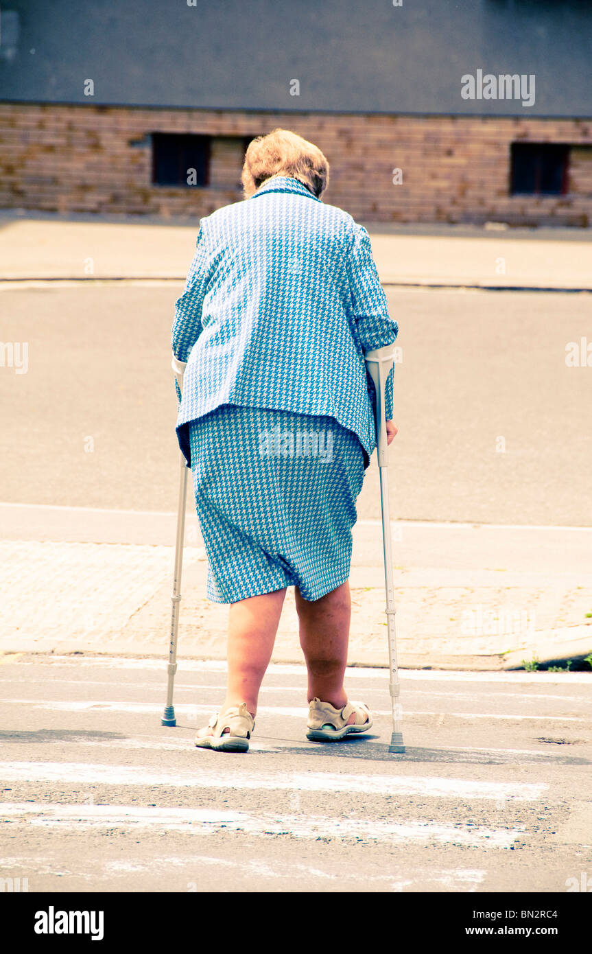 elder woman with crutches crossing a street at a crosswalk - Stock Image
