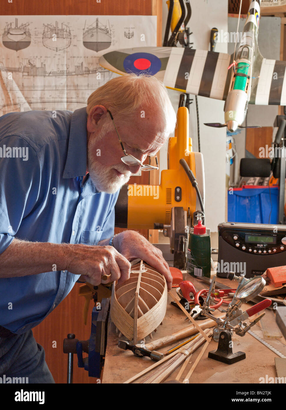 Older man, retiree, making model boat in workshop. UK - Stock Image