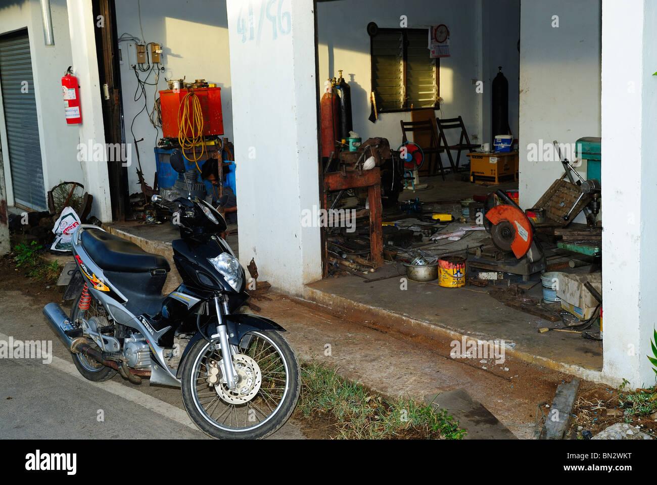 Motorbike parked in a garage in Baan Nam Khen village, West of Thailand - Stock Image