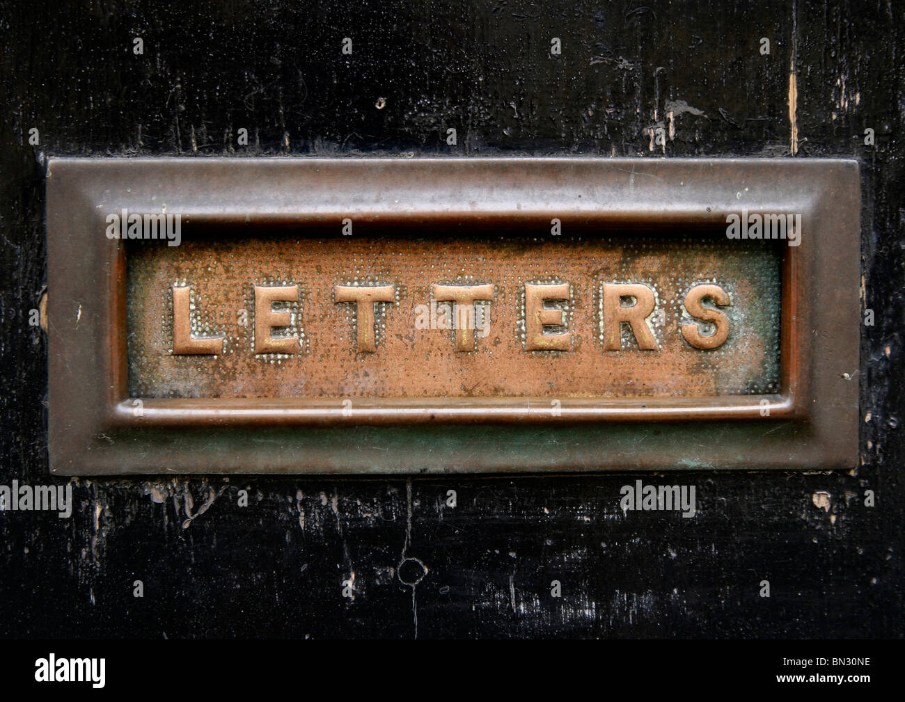 Copper letter box on black door with the word 'Letters' written on it. - Stock Image
