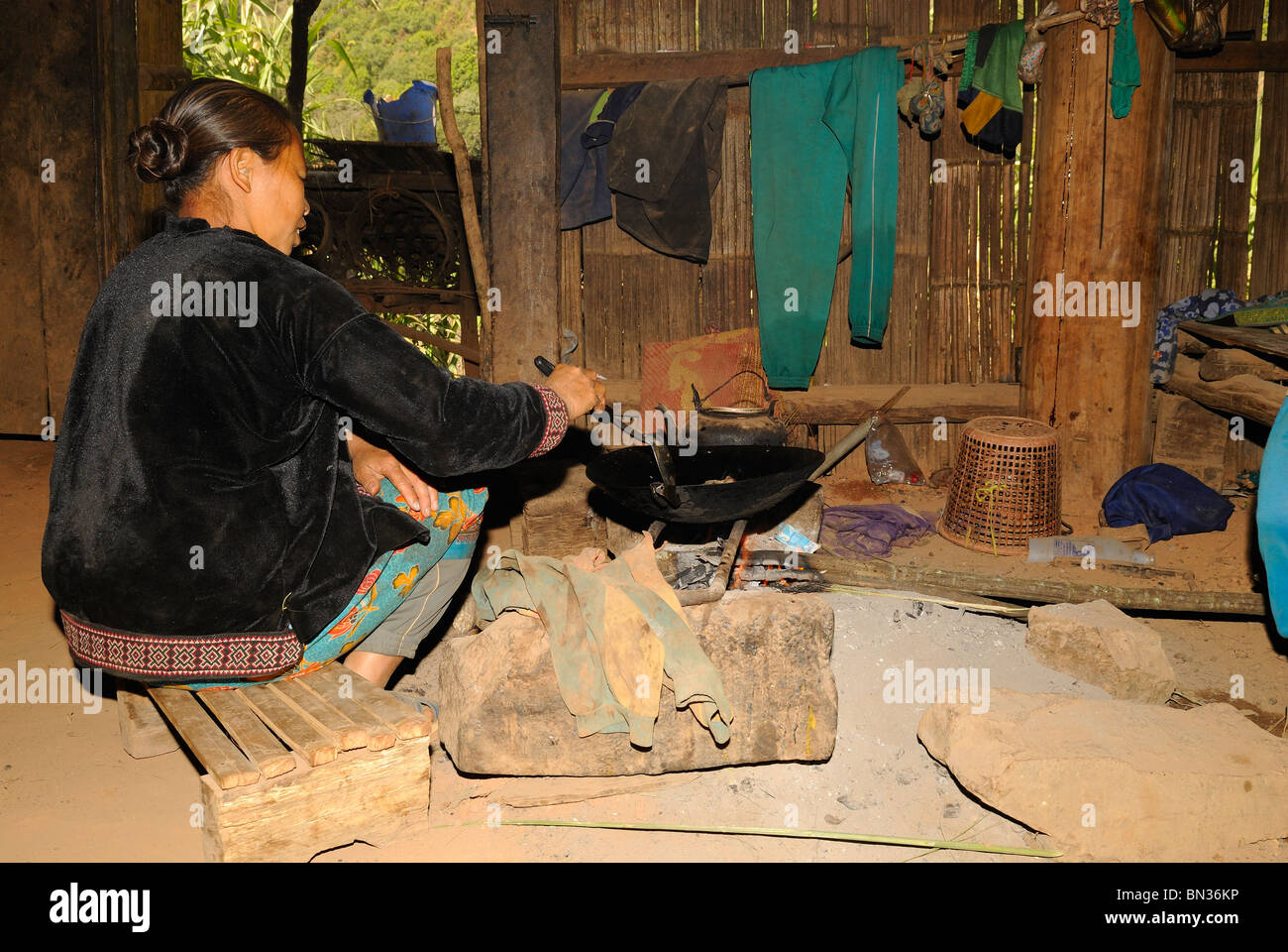 Woman cooking in a pot in her house in a Hmong village, Mae