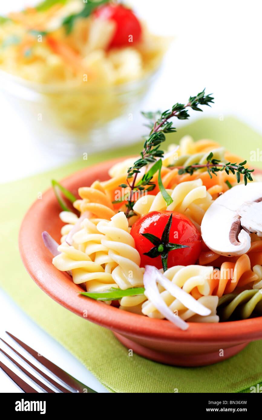 Tricolor corkscrew pasta in a terracotta bowl - Stock Image