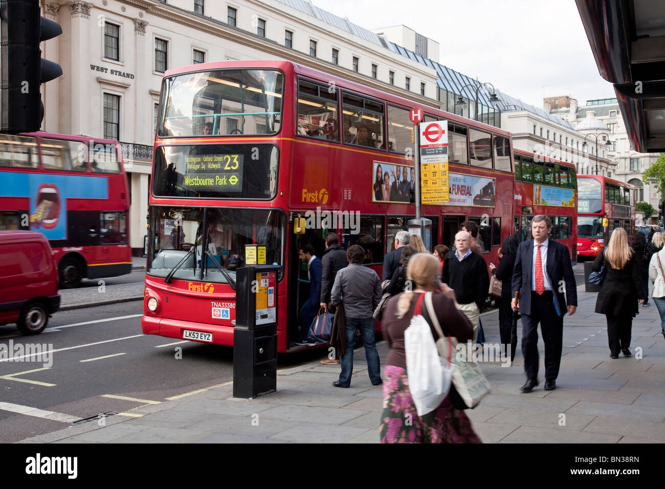 People getting onto a red doubledecker bus in the city centre of London - Stock Image