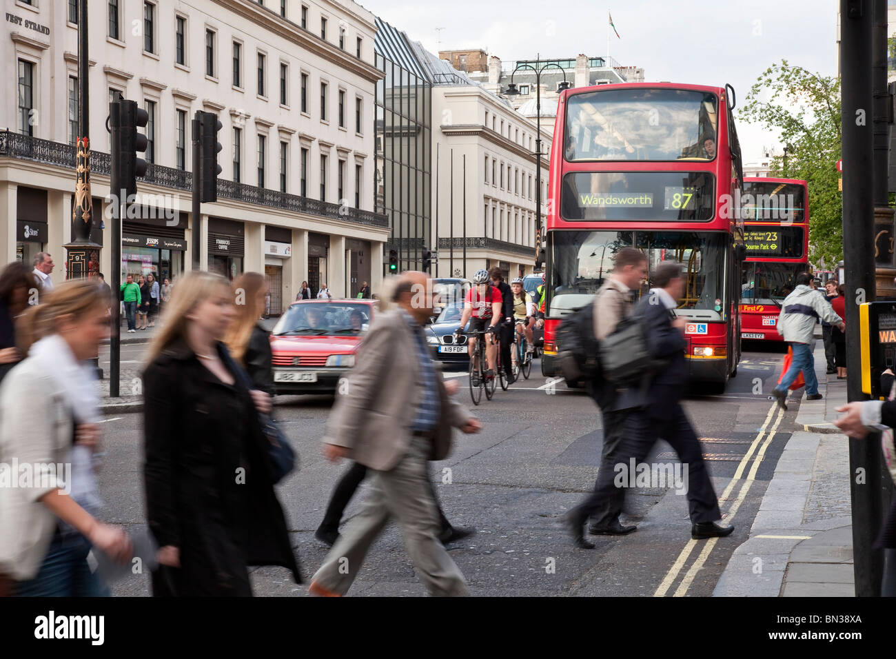 Pedestrians crossing a road, at the back cars, red doubledecker busses and cyclists, London - Stock Image