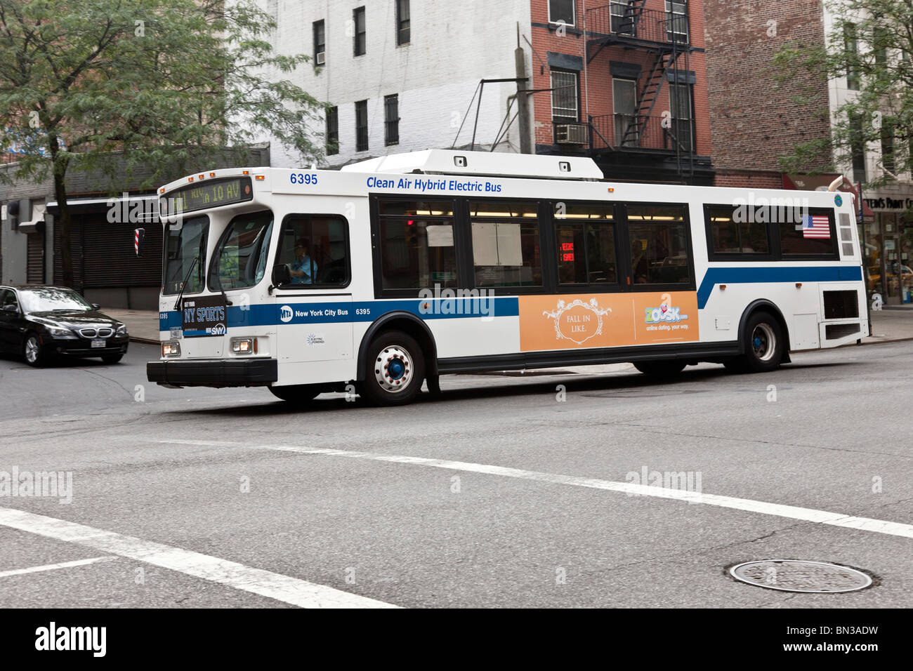 NY Transit Authority hybrid electric bus moves through intersection on West Side Manhattan New York City - Stock Image