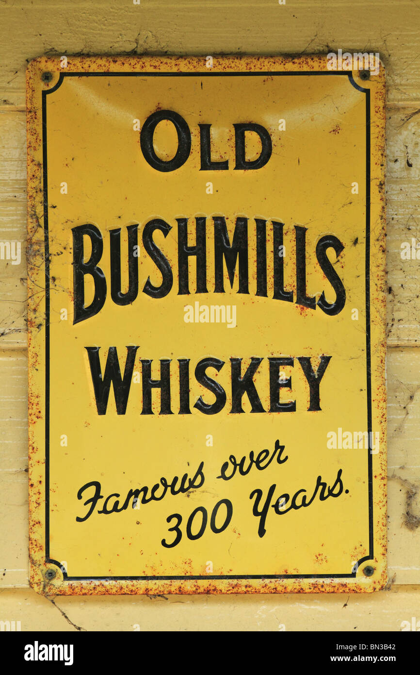 An old Bushmills Whiskey Sign on the external wall of a Pub in County Limerick, Rep of Ireland. - Stock Image
