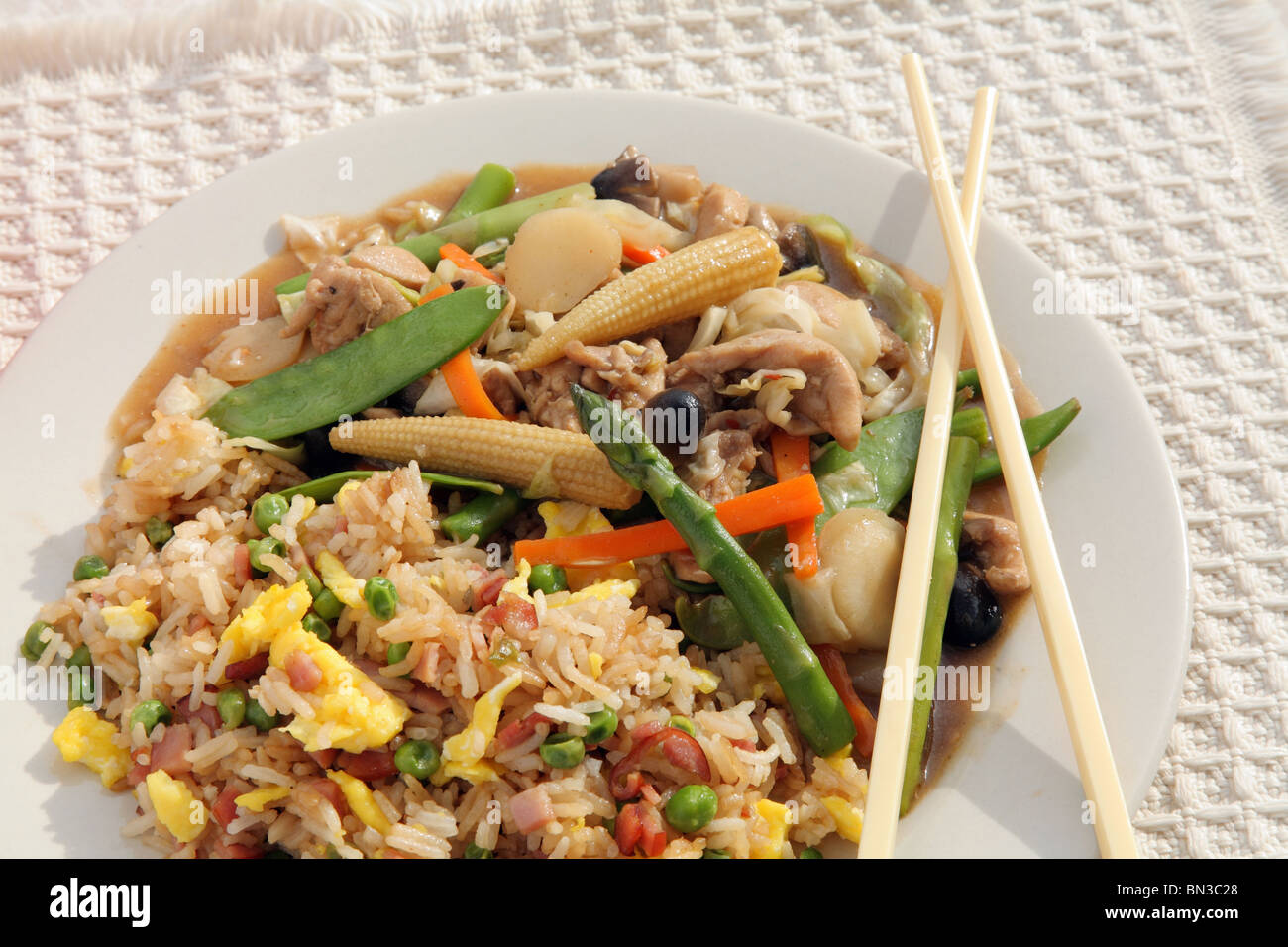close-up plate of colorful Chinese chicken and vegetable stir fry with chopsticks - Stock Image