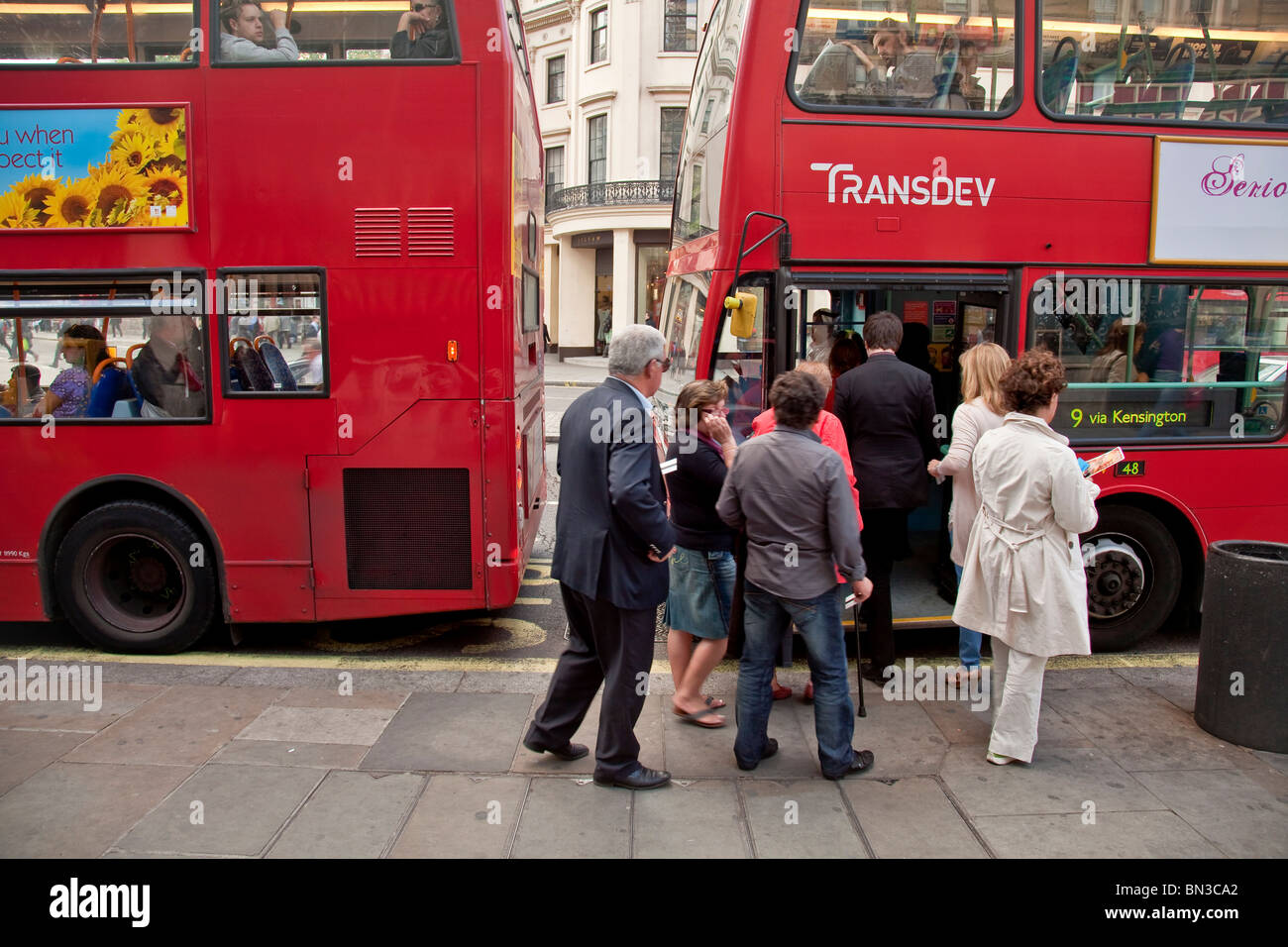 People getting on a typical red doubledecker bus in London - Stock Image