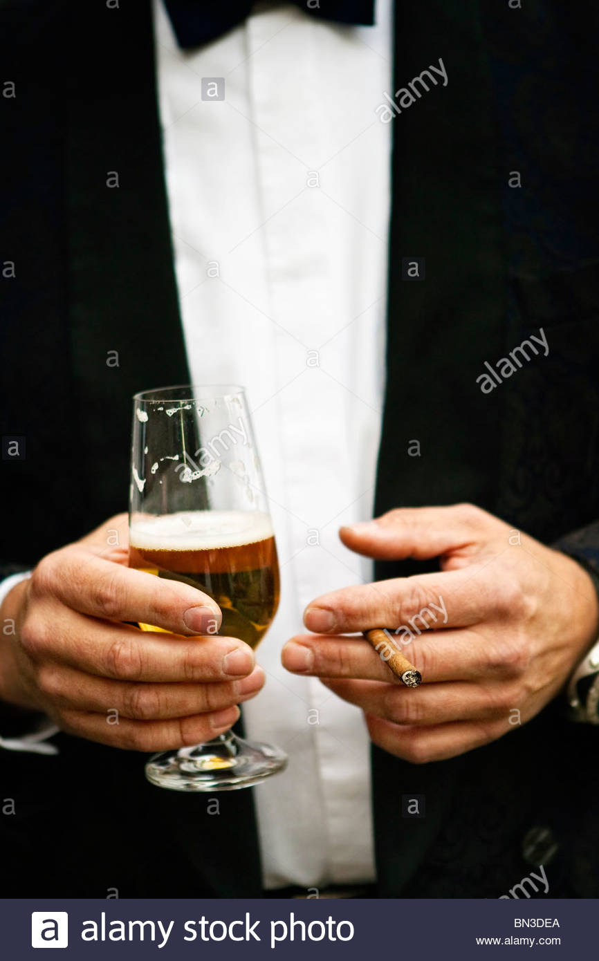 Man holding beer glass and small cigar, mid section - Stock Image