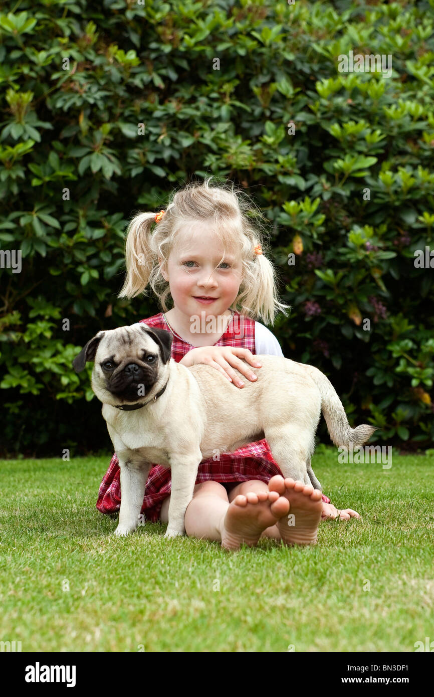 Girl sitting with pug on lawn - Stock Image