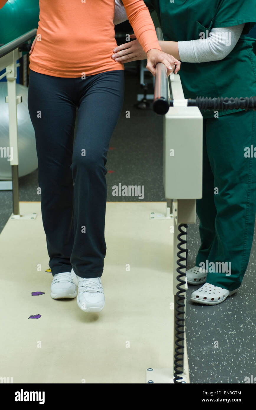 Patient learning to walk and regain leg coordination with assistance from physical therapist - Stock Image