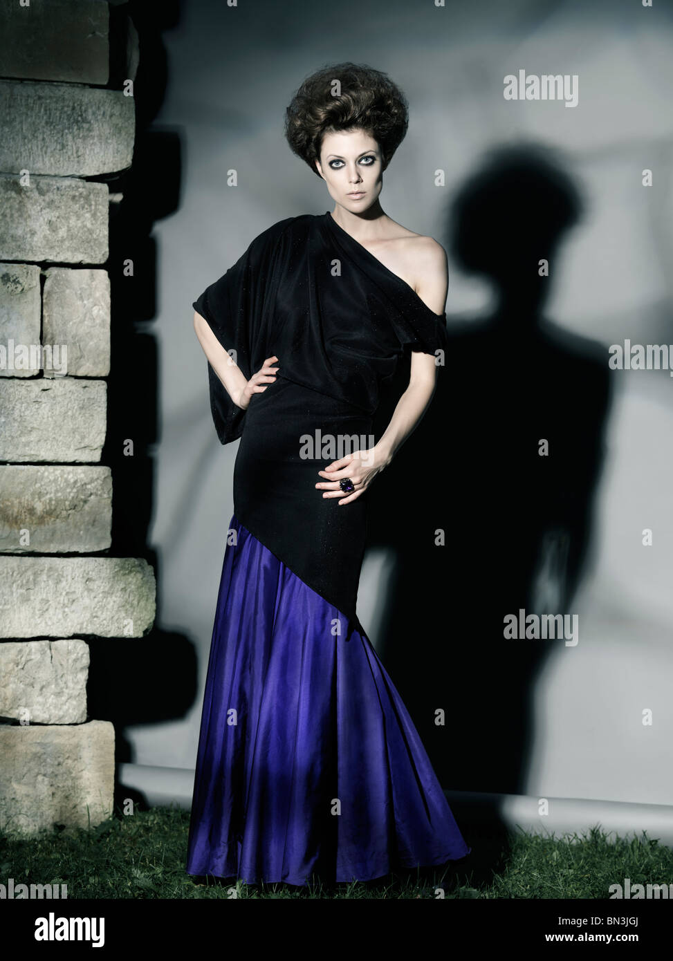 High fashion photo of a beautiful woman wearing elegant long dress - Stock Image