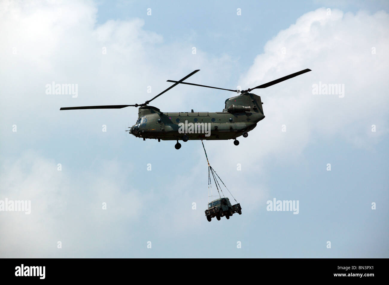 RAF Chinook HC.2 carrying an underslung Landrover and Trailer combo. - Stock Image