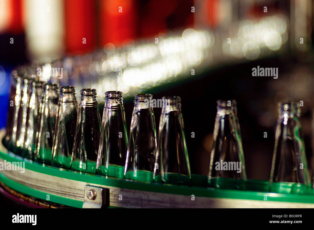 Bottles on production line in manufacturing plant - Stock Image