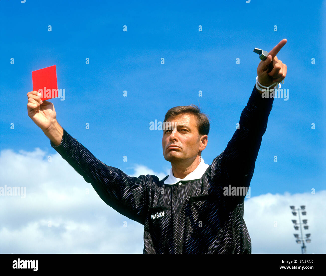 Soccer referee holding up red sending off card - Stock Image