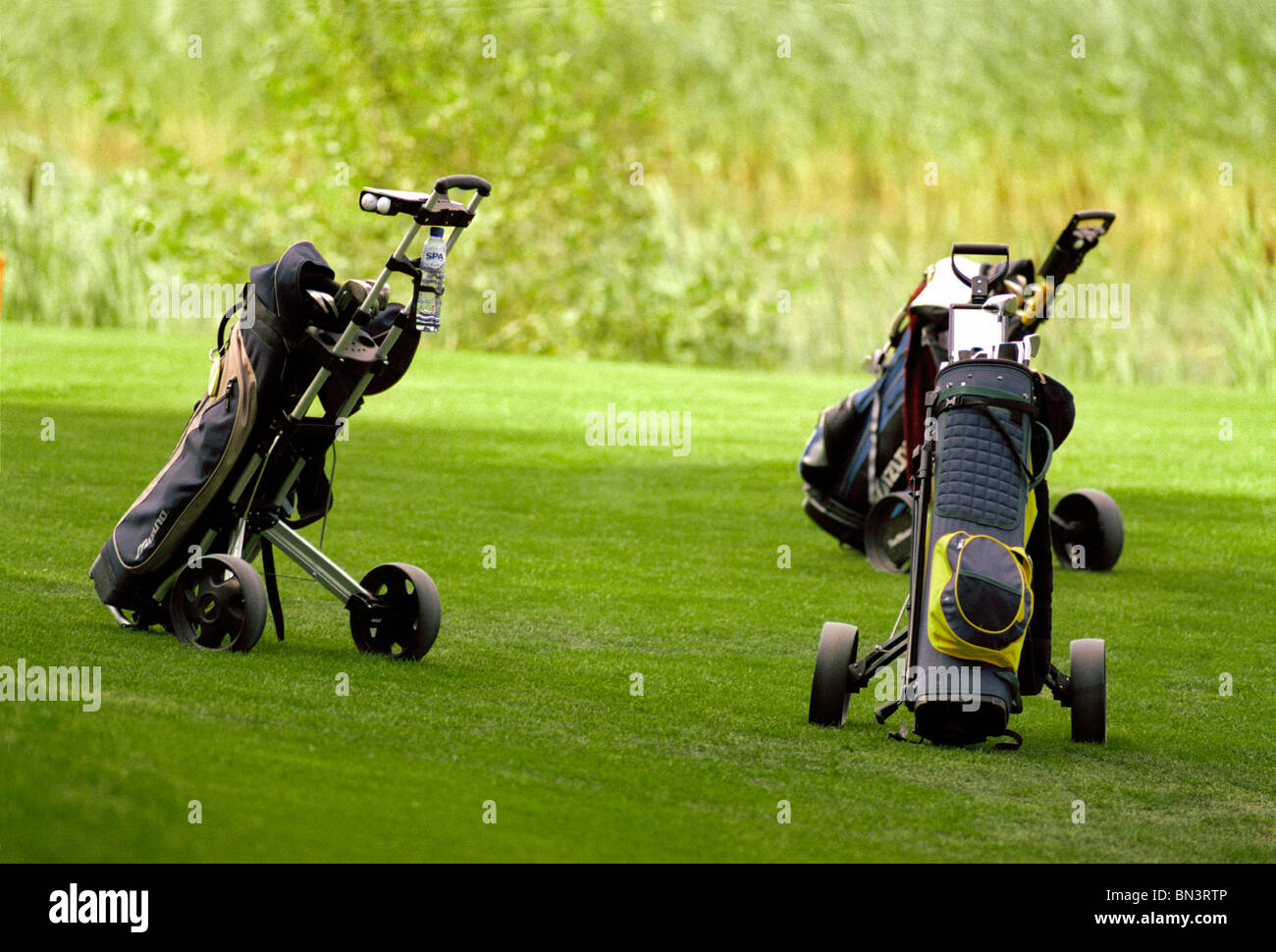 Golf bags on golf course - Stock Image