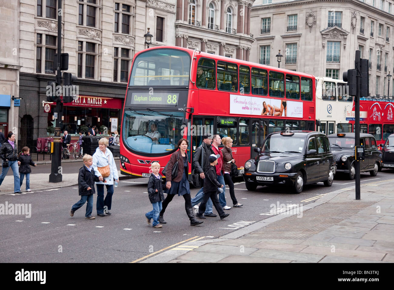 Street scene in the centre of London with black taxi cab and red doubledecker bus, London - Stock Image