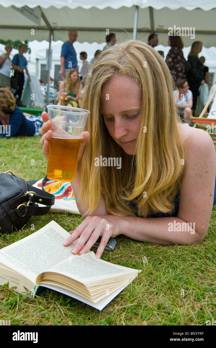 Young woman reading book lying on grass holding pint of lager at Hay Festival 2010 Hay on Wye Powys Wales UK - Stock Image