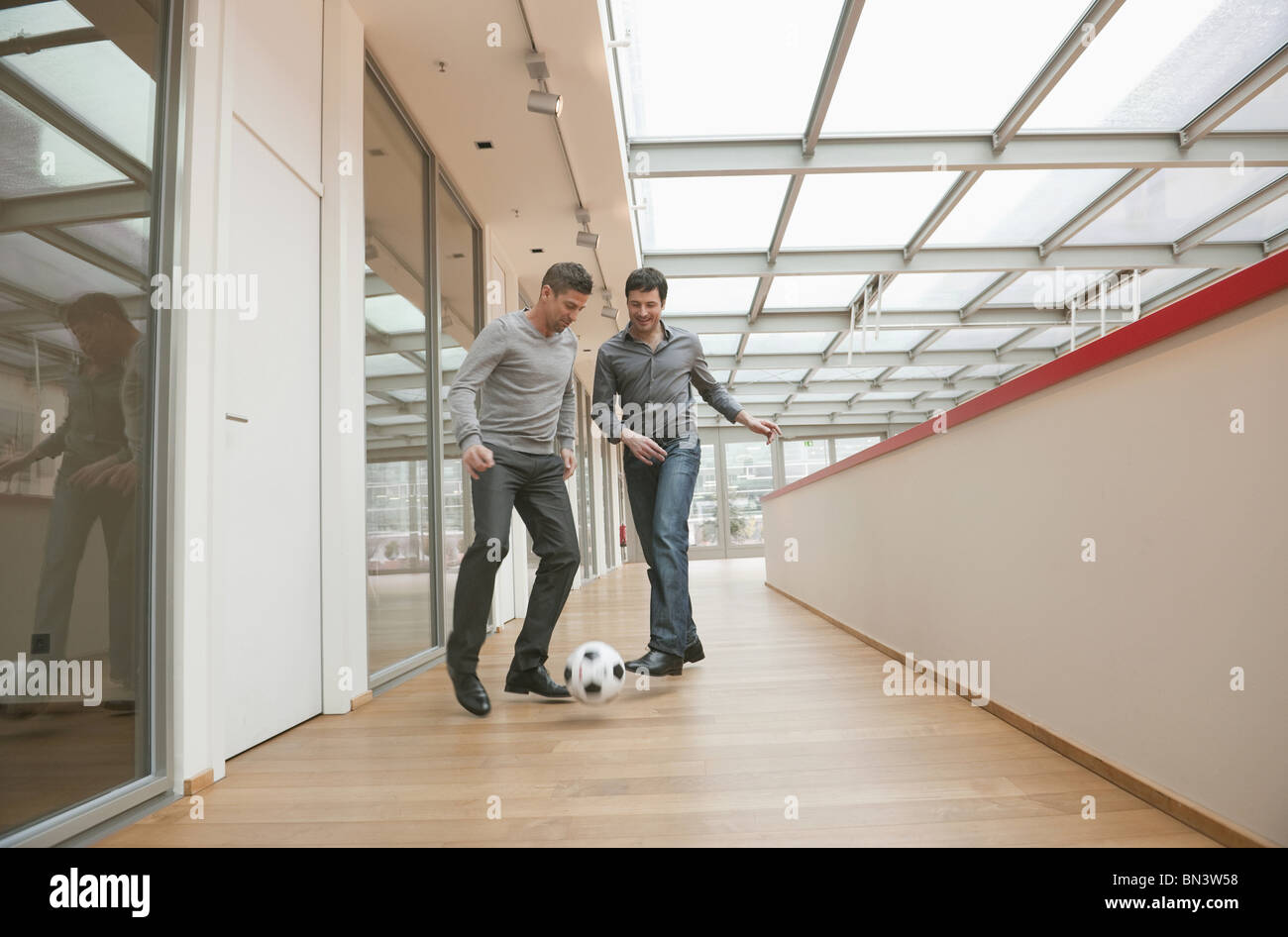 two business men playing soccer in office building