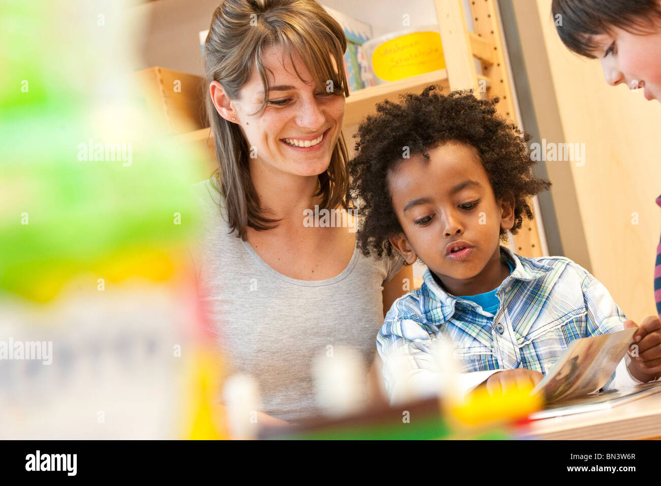 Kindergarten teacher and children looking at book, low angle view - Stock Image