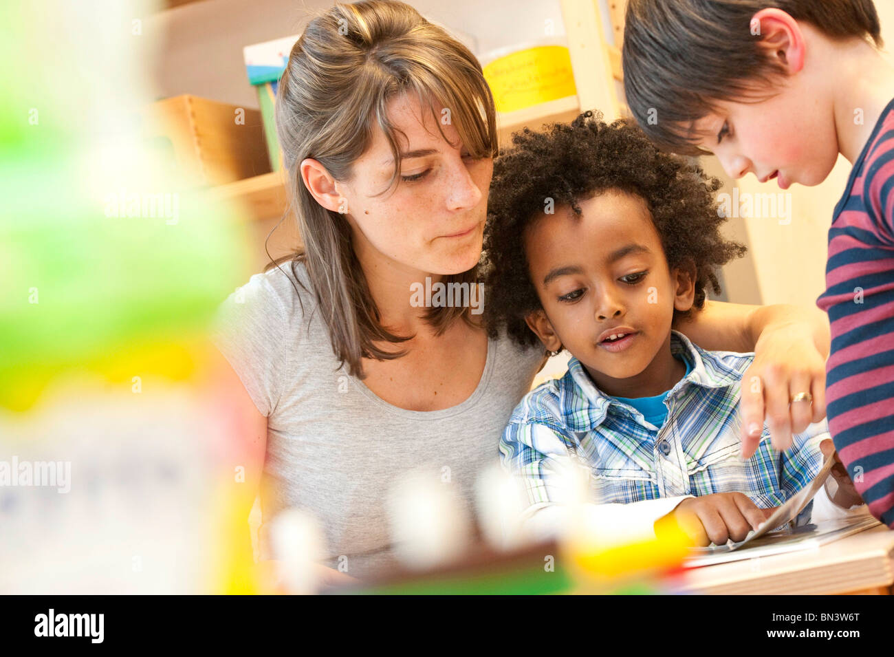 Kindergarten teacher and children looking at book, low angle view Stock Photo