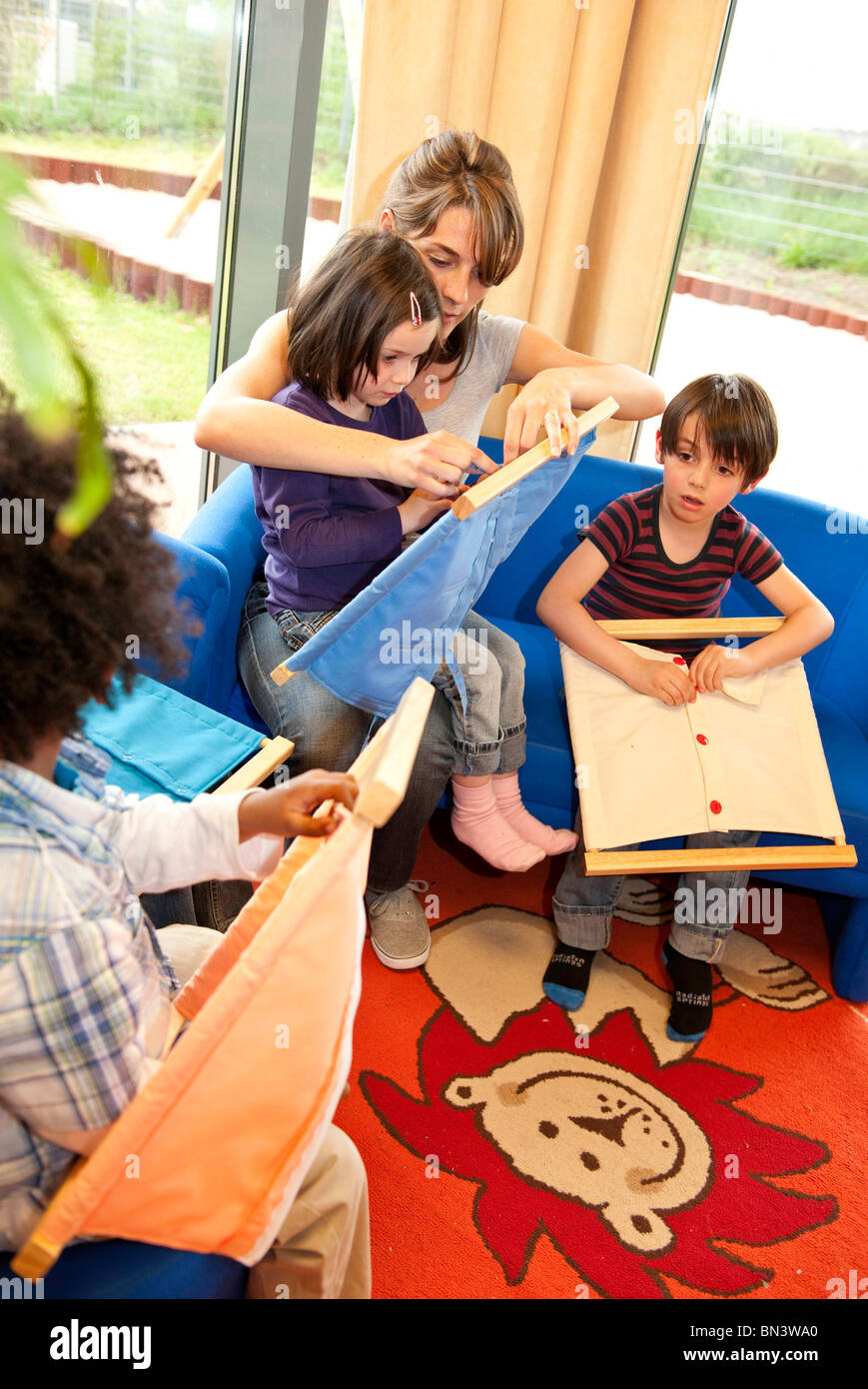 Kindergarten teacher and children playing fasteners frames, elevated view Stock Photo