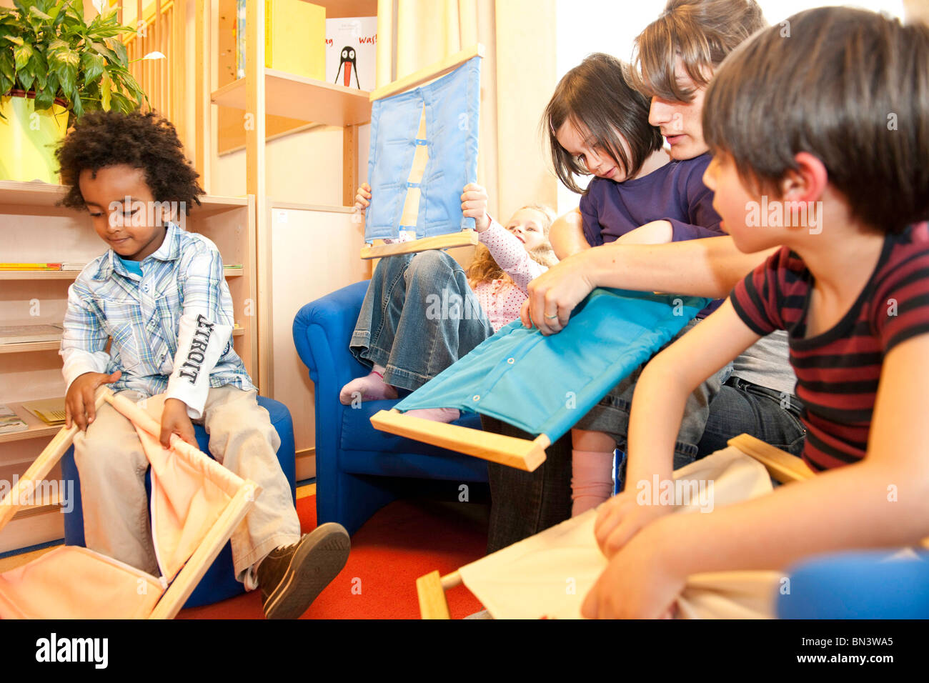 Kindergarten teacher and children playing fasteners frames - Stock Image