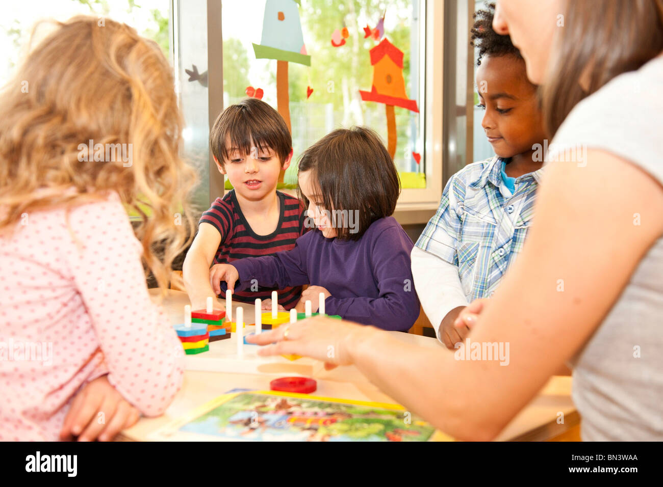 Kindergarten teacher playing children - Stock Image