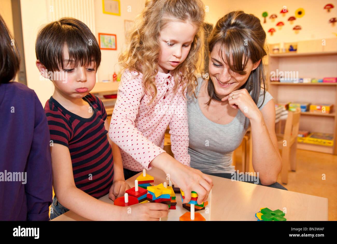 Kindergarten teacher playing children - Stock Image